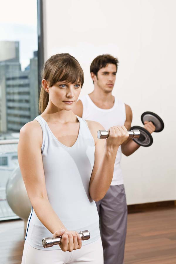 Man and woman working out with dumbbells.