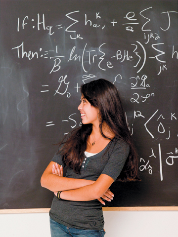 smiling girl at blackboard with math equations on it